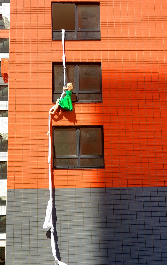 The stuntwoman descends from the window