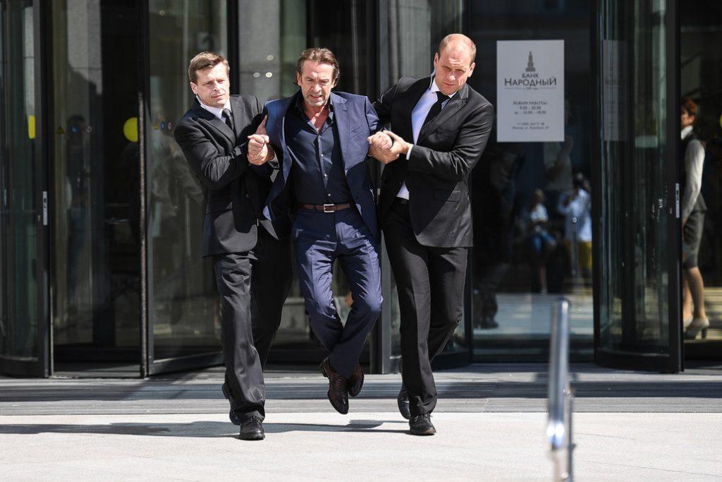 Каскадеры выносят актера Владимира Машкова из банка.